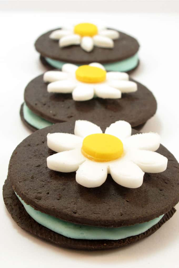 vegan sandwich cookies: Chocolate wafers, icing, and daisy flower fondant toppers. #SandwichCookies #ChocolateWafers #SpringDesserts #Daisy #Fondant #VeganCookies