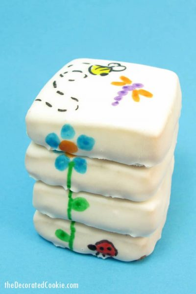 Stacked flower cookies for Spring with poured sugar icing and designs hand-drawn with food coloring pens.