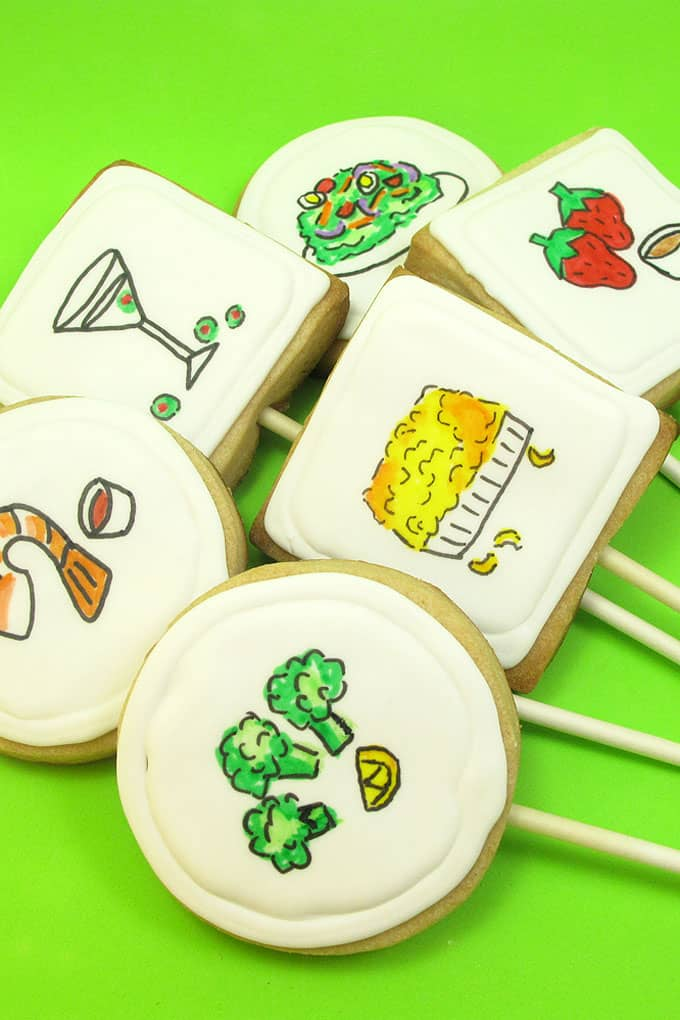 "Dinner cookies: How to use food coloring pens to draw ""dinner"" on royal icing topped cookies on a stick."