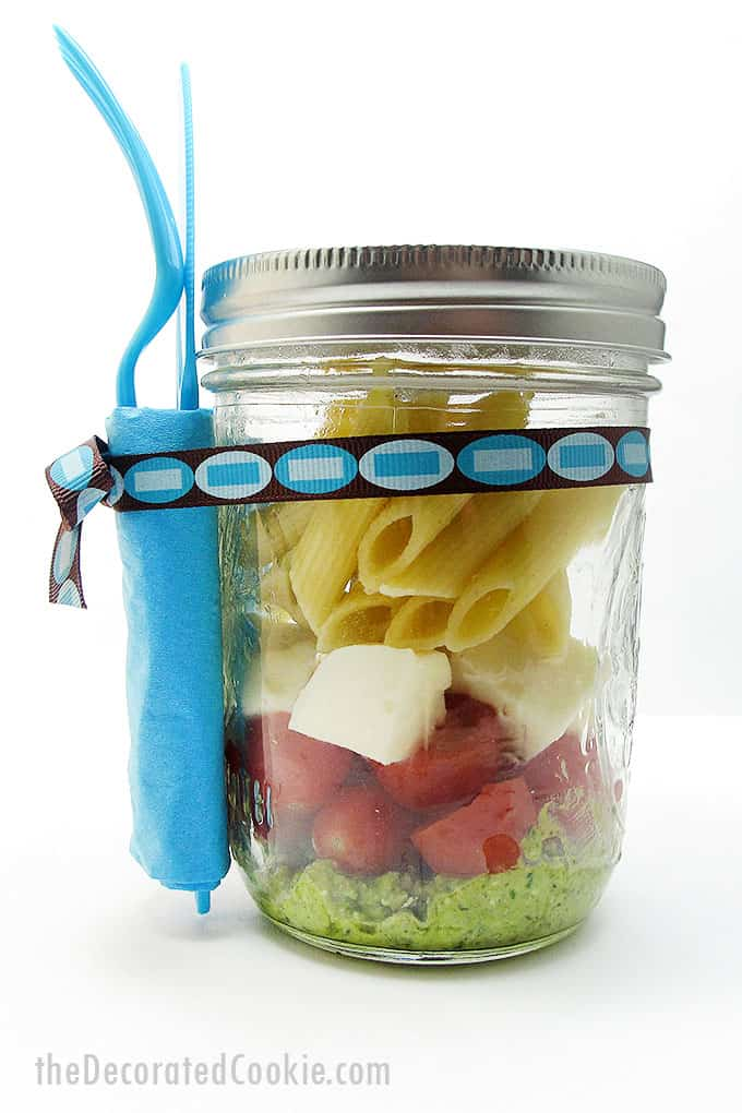 pesto pasta salad in a mason jar with fork and knife