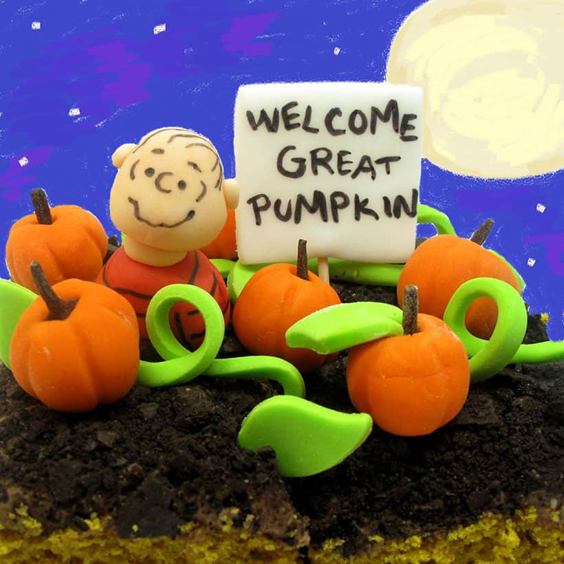 pumpkin cake with chocolate cream cheese frosting decorated with Linus and the great pumpkin patch