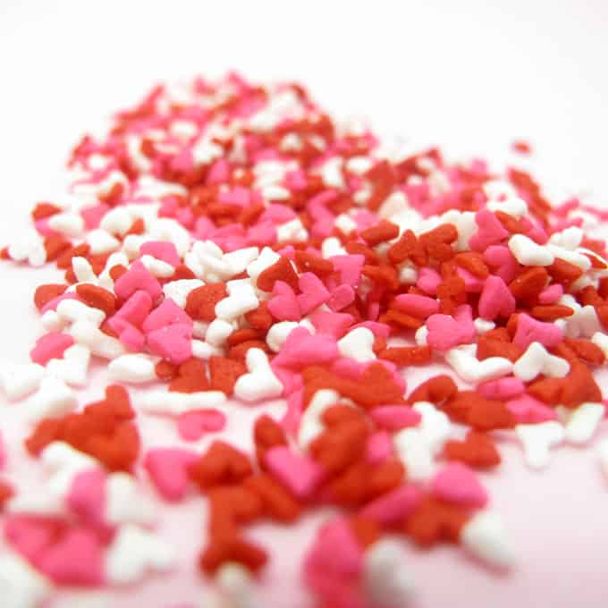Heart sprinkle marshmallows and cookies with royal icing for easy Valentine's Day treats.