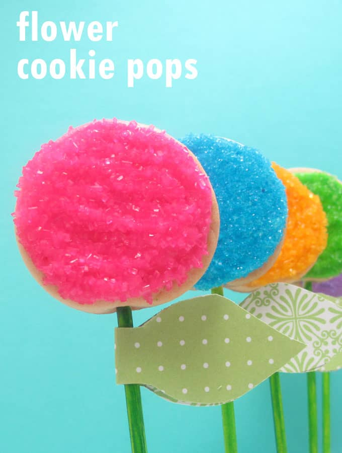 How to decorate easy flower cookie pops using sprinkles. Attach paper leaves to make place cards or party favors for a spring or garden party.