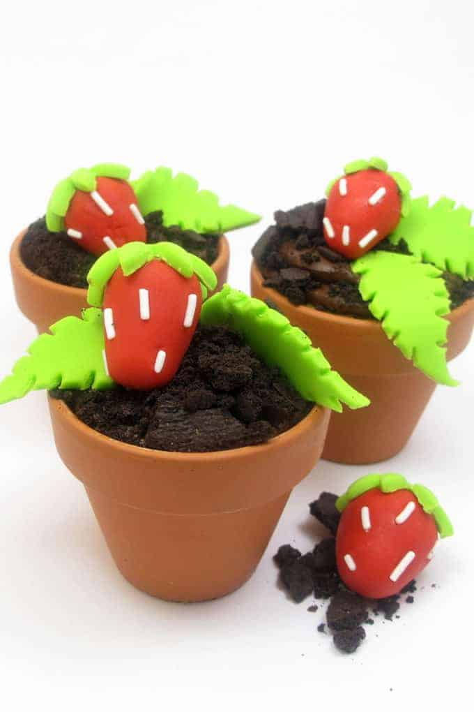 "Strawberry patch cupcakes are delicious chocolate ""dirt"" cupcakes in flower pots with strawberry patch fondant decorations.  #strawberry #summer #cupcakes #flowerpot #Fondant"