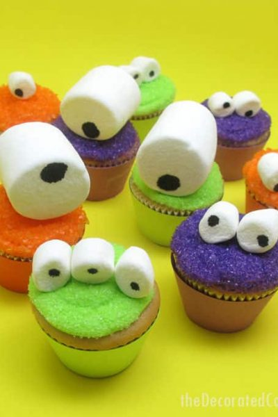 Mini monster cupcakes for a fun Halloween food idea -- marshmallow googly-eyes top sparkly cupcakes. Easy cupcake decorating.