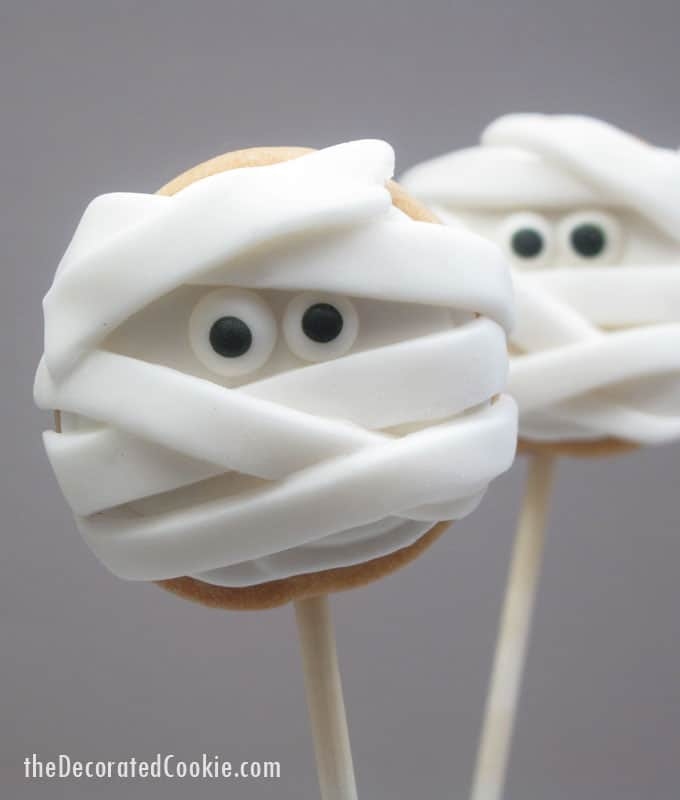 Halloween mummy cookies on a stick: Simple iced cookie pops topped with strips of fondant and candy eyes becomes spooky mummy cookies!