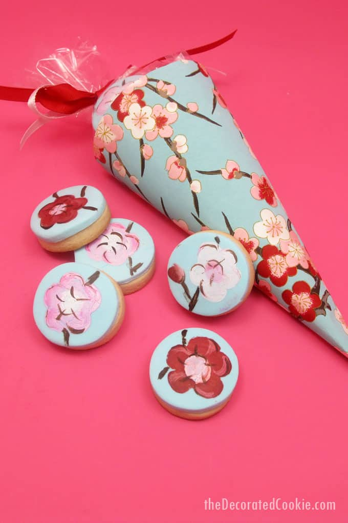 How to make painted cherry blossom decorated cookies in paper cones for beautiful spring party favors.  #papercones #weddingfavors #paintedcookies #cherryblossoms #flowers #partyfavors #fondant