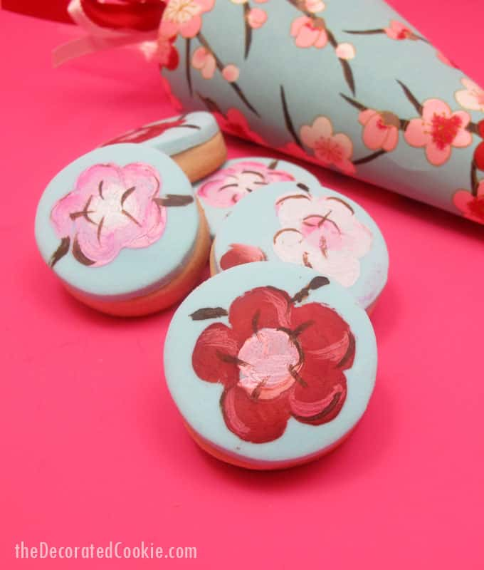 How to make painted cherry blossom decorated cookies in paper cones for beautiful spring party favors.  #papercones #weddingfavors #paintedcookies #cherryblossoms #flowers #partyfavors #fondant #spring