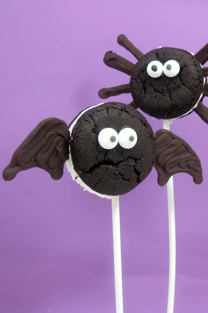 Oreo Cakester bat and spider pops for Halloween. Store-bought cookies, chocolate, and sticks for an easy Halloween party food idea.