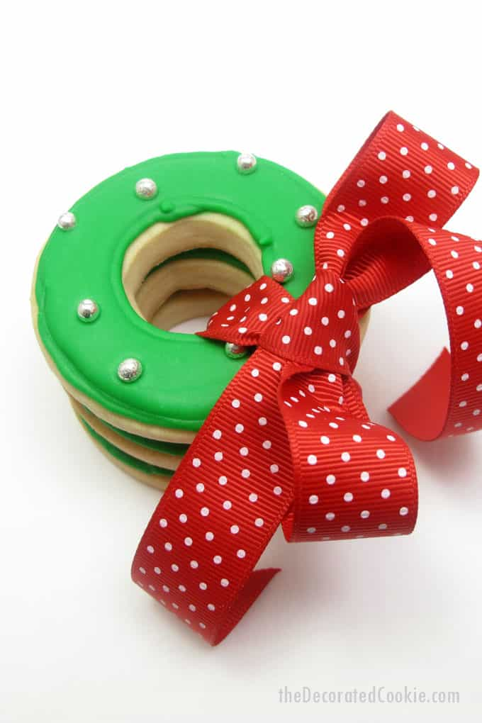 These Christmas wreath cookies are so simple and pretty easy to decorate using circle cookie cutters, one color of icing, and silver dragees,