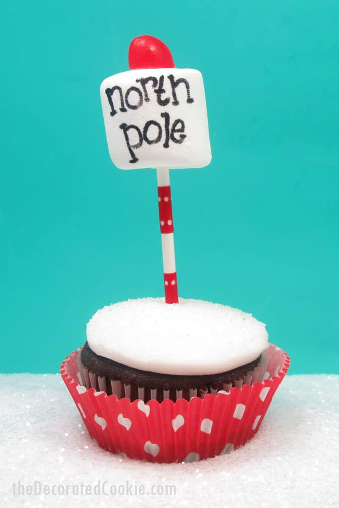 Super simple North Pole cupcakes for a cute and easy Christmas treat. Cupcakes, white frosting, a lollipop stick, marshmallow, food writer, and candy.