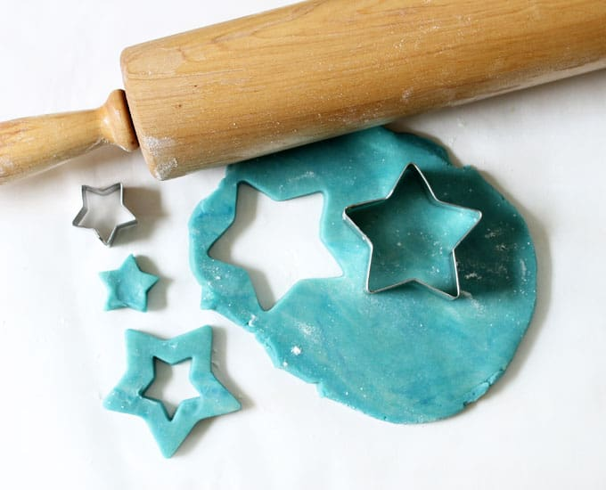 rolling out blue dough for Pop Rocks star cookies, 4th of July sandwich cookies
