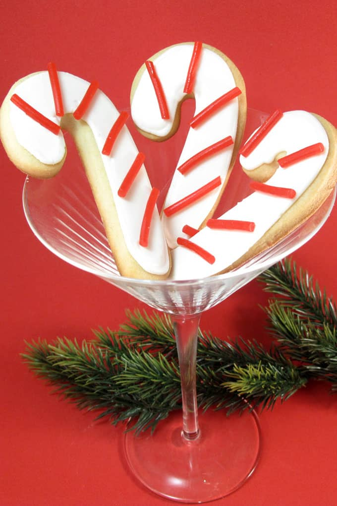 This simple candy cane cookies are classics to make for Christmas. By using licorice for the stripes, you only need one color if icing, simplifying things.