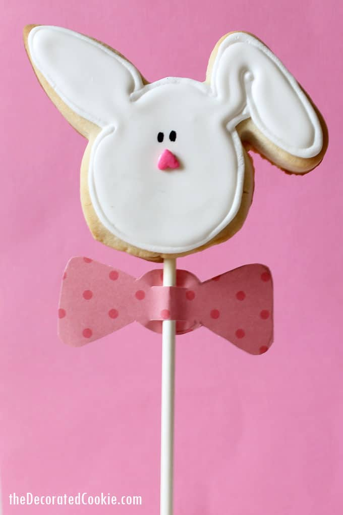 Decorated EASTER BUNNY COOKIES on a stick wearing paper bow ties. How to decorate cookies for Easter with step-by-step instructions.