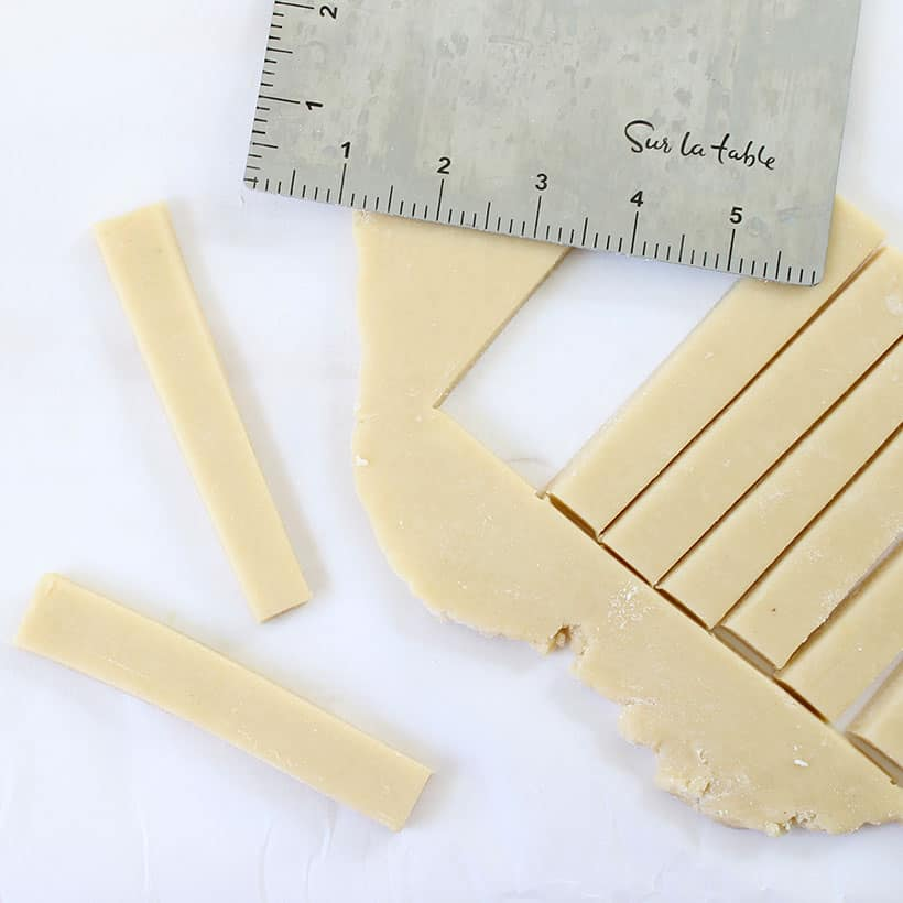cutting out turkey cookie sticks from rolled out cookie dough