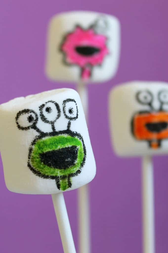 Monster marshmallows for Halloween. Use food coloring pens and marshmallows to create marshmallow art for an easy Halloween treat idea kids can make.