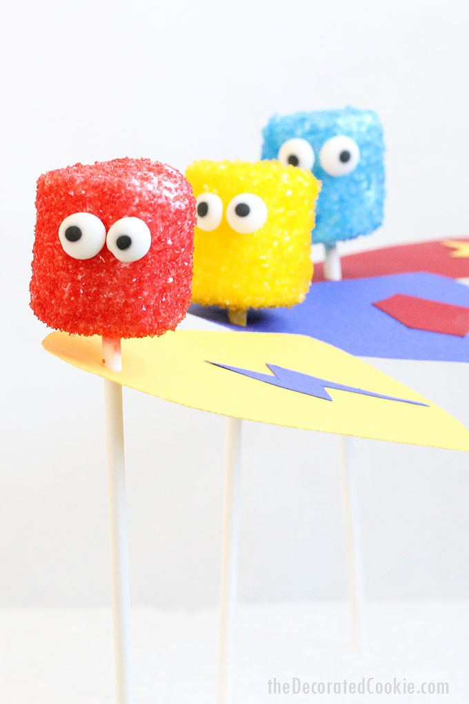 SUPERHERO MARSHMALLOW POPS -- Easy treat using sprinkles, candy eyes, and paper. Perfect food idea for superhero parties.