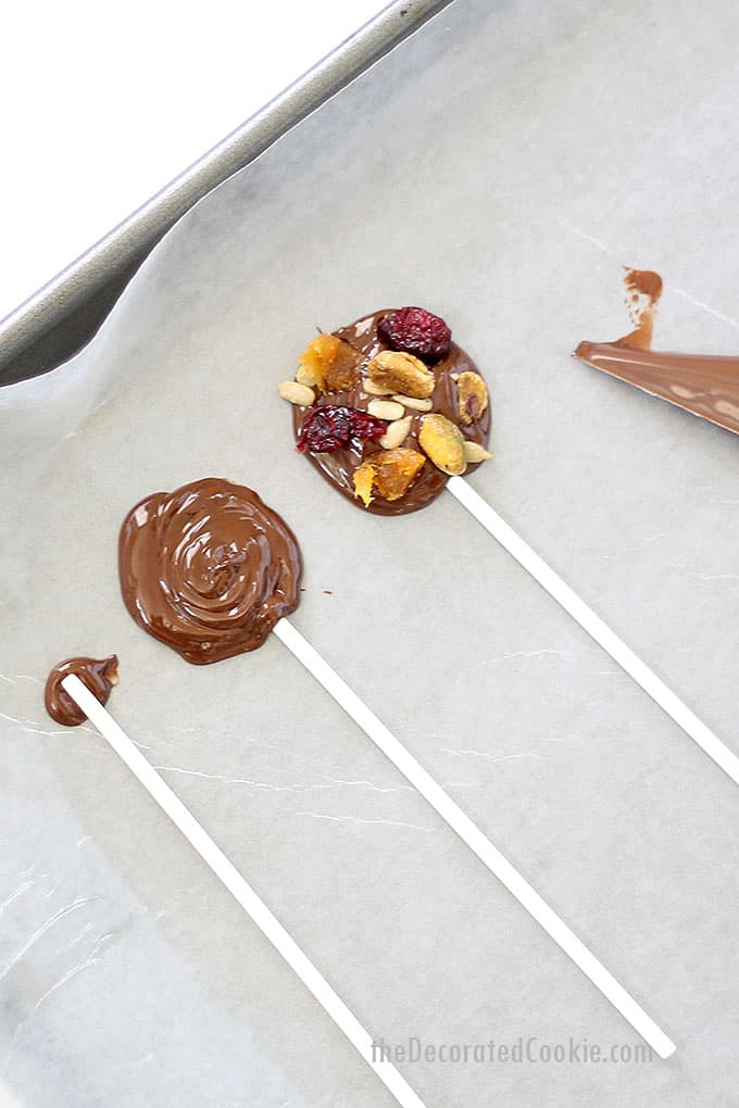 piping dark chocolate pops with fruits, nuts, and seeds