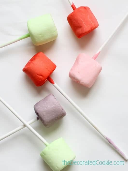 Pour a packet of Kool-Aid (about 1 tablespoon) in a glass or small mason jar. Mix in 1/4 to 1/2 cup water, or enough so the marshmallow can be submerged. Skewer a marshmallow with a lollipop. Submerge the marshmallow in the Kool-Aid for 10 to 15 seconds. Remove and prop in a Styrofoam block. Use a paper towel to catch drips. Let the marshmallow pops dry for 15 minutes. The color will set and deepen as the marshmallow dries. If desired, store in the refrigerator.