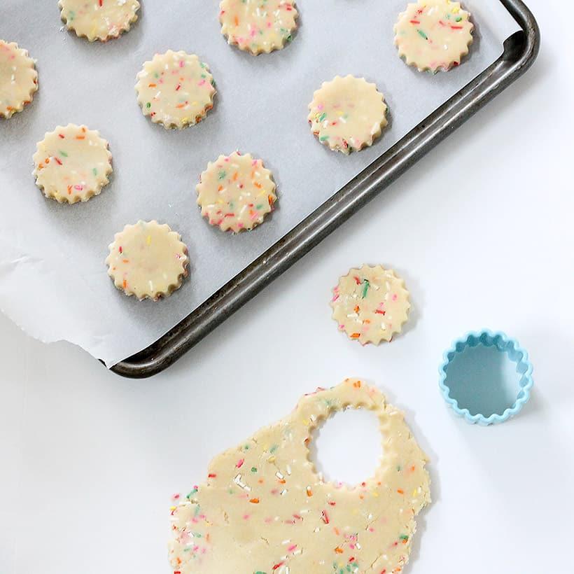 rainbow sprinkle shortbread cookies on baking tray