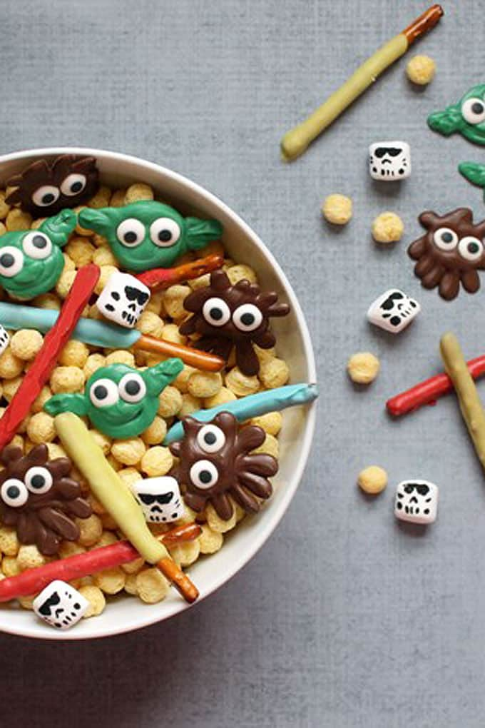 This easy, delicious Star Wars snack mix is a fun party food idea. Mix cereal, Storm Trooper marshmallows, candy yoda and Chewbacca, pretzel light sabers.