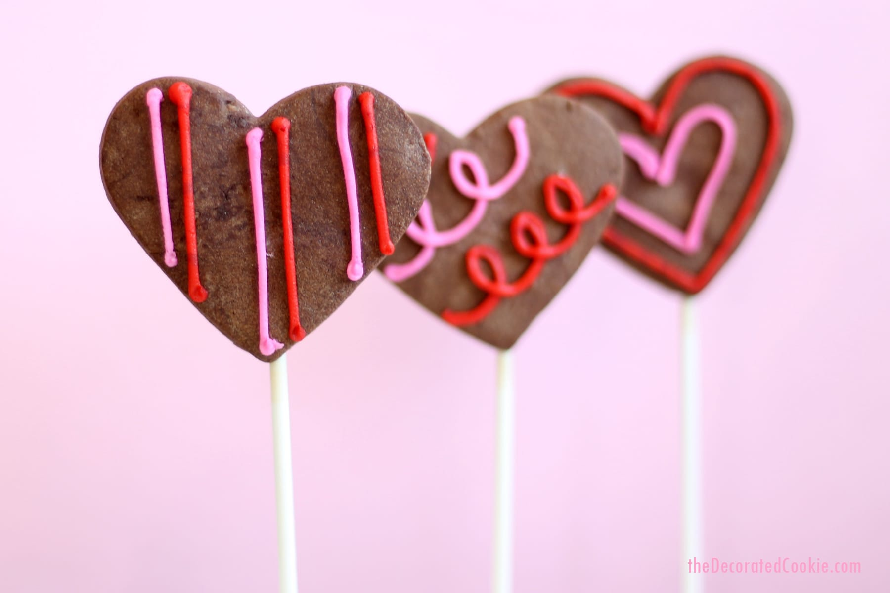 chocolate heart cookie pops with orange buttercream frosting