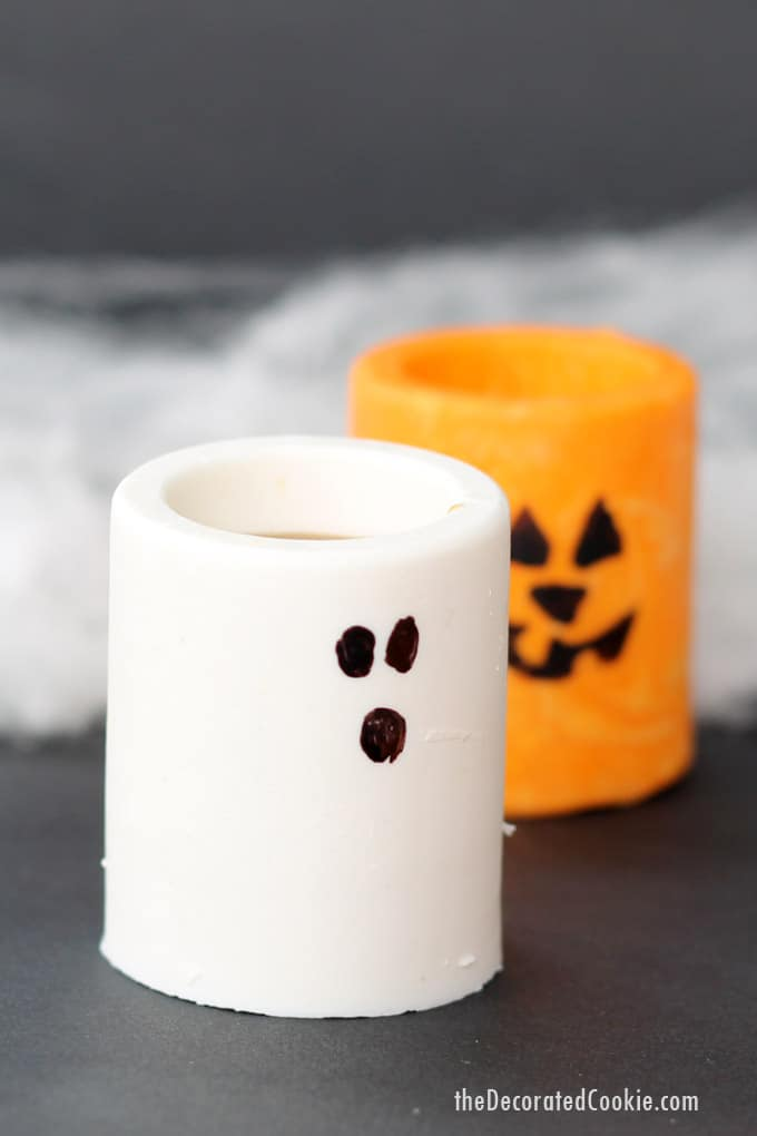 Chocolate ghosts and Jack O' Lantern edible Halloween shot glasses or treat cups to make your Halloween party extra fun -- Halloween party drinks. #candyshotglasses #edibleshotglasses #halloween #partyfood #partydrinks #halloweendrinks #chocolate #ghosts #jackolantern