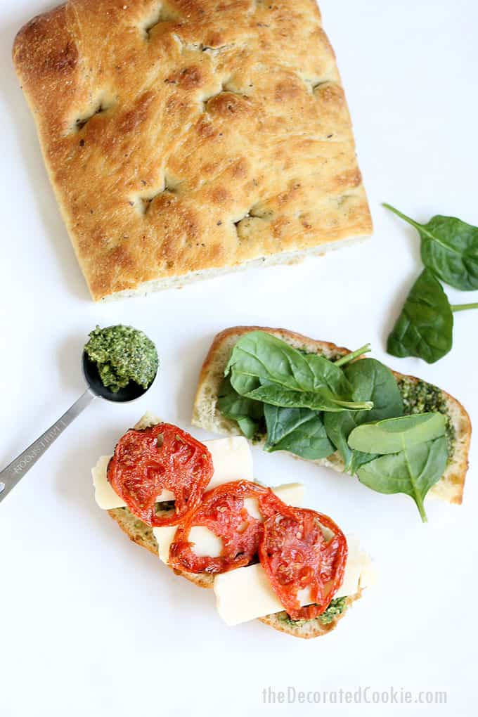 Make a homemade Starbucks panini with roasted tomatoes, pesto, spinach, and mozzarella cheese. A delicious lunch idea. Starbucks sandwiches.
