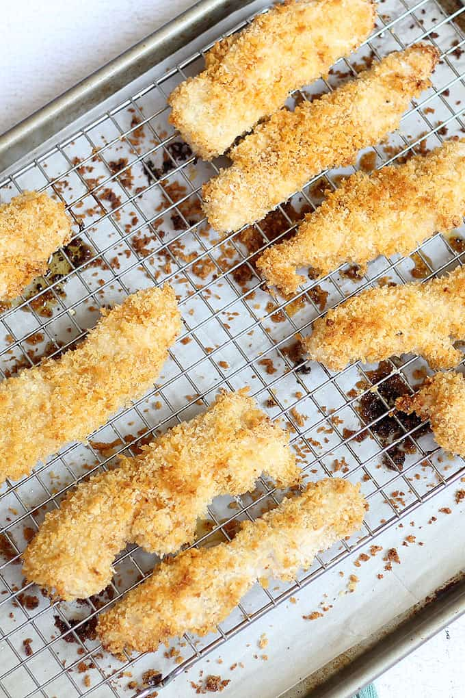 Tips and tricks to make extra crispy baked chicken strips with panko bread crumbs. An easy weeknight dinner idea.Video recipe included.