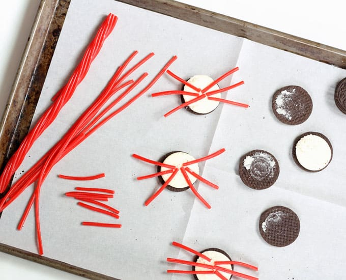 making Oreo crabs with red candy melts and licorice legs