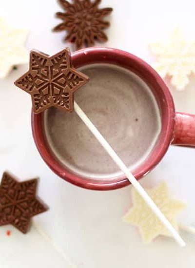 Snowflake hot chocolate on a stick with Wilton candy melts, snowflake silicone mold, and Wilton sprinkles. Just stir into milk! Great homemade gift idea for Christmas and the holidays. Package as stocking stuffers, school bake sale idea.
