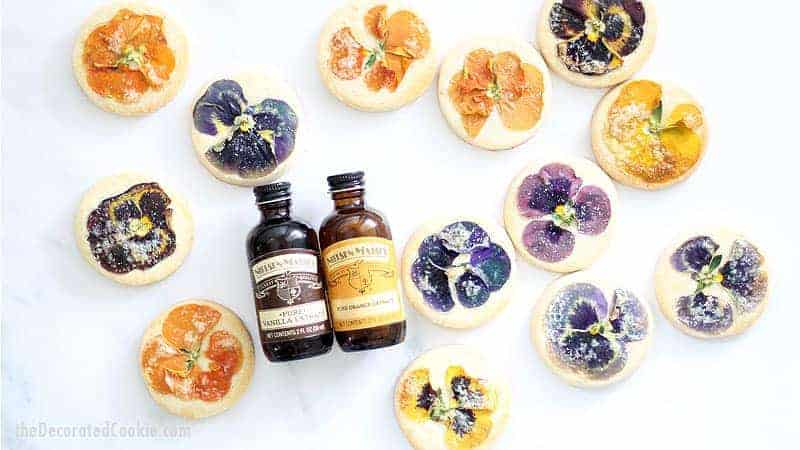 These gorgeous orange cookies with edible flowers are delicately flavored with orange extract and topped with a sprinkle of sugar. For afternoon tea, a lovely gift, or just to enjoy, these floral cookies are just right. These cookies use Nielsen-Massey's Pure Vanilla Extract and Pure Orange Extract. (Sponsored by Nielson-Massey) #NielsenMasseyPartner