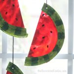 This watermelon suncatcher, made with melted crayons and paper plates, is a fun summer craft kids and adults can make together. #suncatcher #kidscraft #summercrafts #summer #watermelon