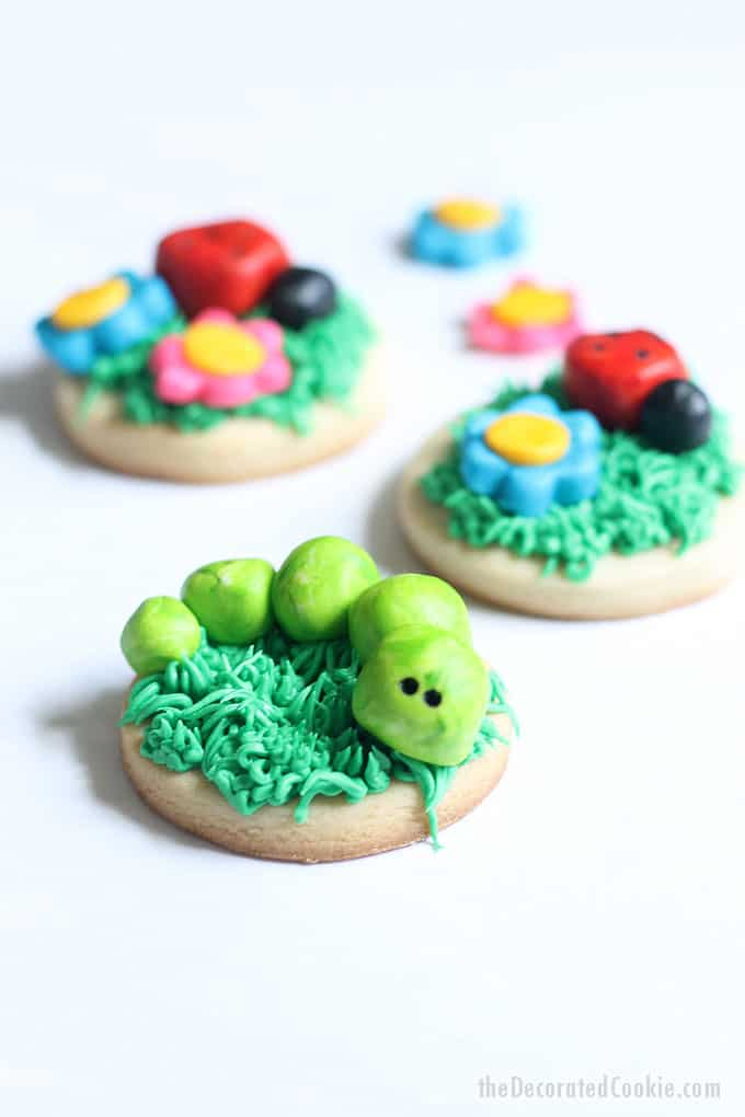 FROSTING CLAY: How to turn buttercream frosting into a delicious alternative to fondant. Sculptable frosting is perfect for cake and cookie decorating. Here, I made grass-topped decorated cookies with buttercream frosting clay BUGS and FLOWERS. #cookiedecorating #buttercreamfrosting #candyclay #fondant #cookies #bugs