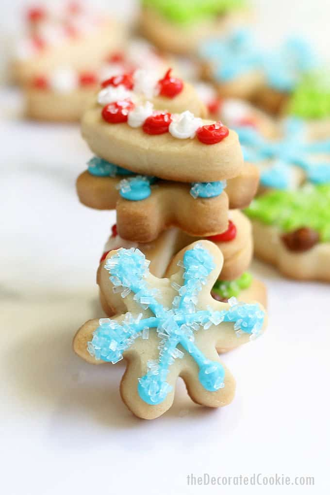 These sparkly MINI CHRISTMAS COOKIES are topped with sprinkles and easy to decorate. Package in tins for a holiday gift idea. #christmascookies #cookiedecorating #minichristmascookies #christmastree #snowflakecookies #candycanecookies