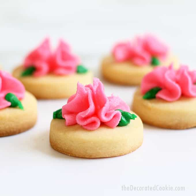 MINI ROSE COOKIES -- Simple buttercream frosting flowers on bite-size cut-out sugar cookies are a pretty and pink Valentine's Day cookie idea. #valentinesday #cookiedecorating #rosecookies #flowers #pink #frosting