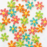 How to decorate MINI DAISY COOKIES with royal icing on cut-out sugar cookies. Colorful flower cookies for Spring or Mother's Day. Package in mason jars for a homemade gift idea.