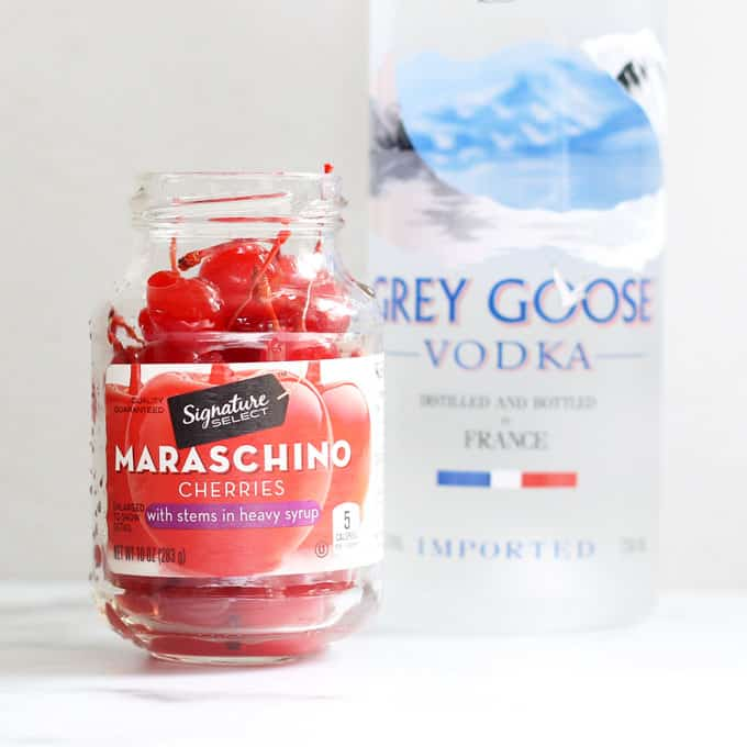 jar of maraschino cherries and bottle of grey goose vodka