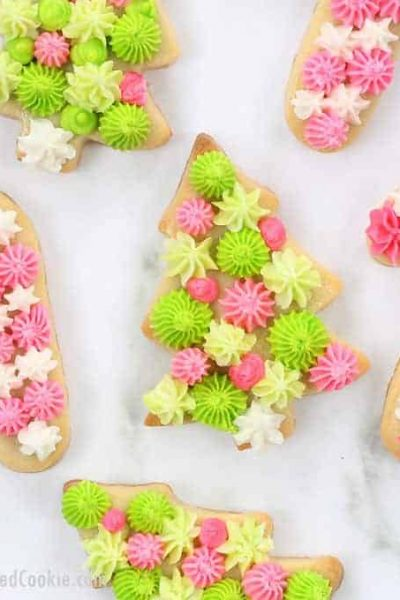 Christmas tree and candy cane cookies with pink and green buttercream frosting decoration