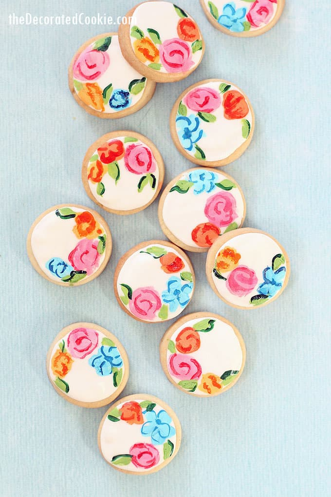 overhead view of painted flower cookies on blue background