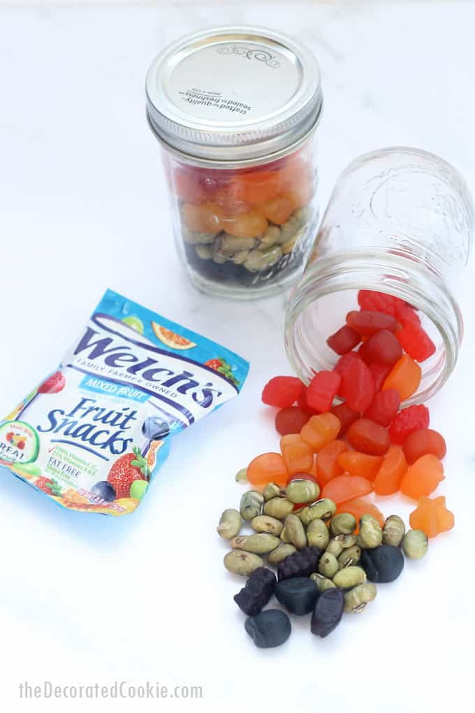 filling view of rainbow snack mix mason jars