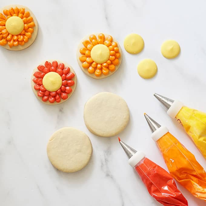 cookies and decorating bags with frosting for piped fall flower cookies