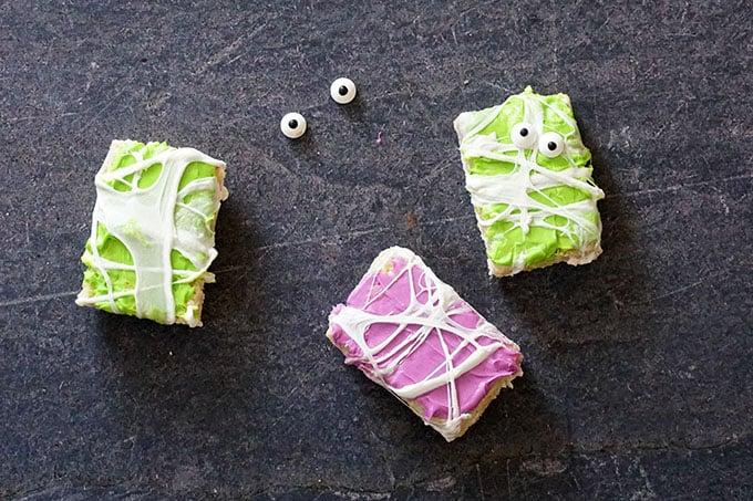 overhead image of adding candy eyes to halloween rice krispie treats