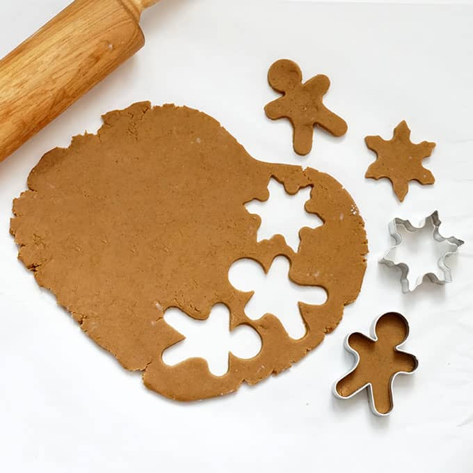 cutting out gingerbread cookies with rolling pin and cookie cutters