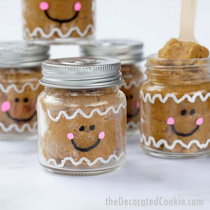 close-up edible gingerbread cookie dough in little mason jars painted as gingerbread men
