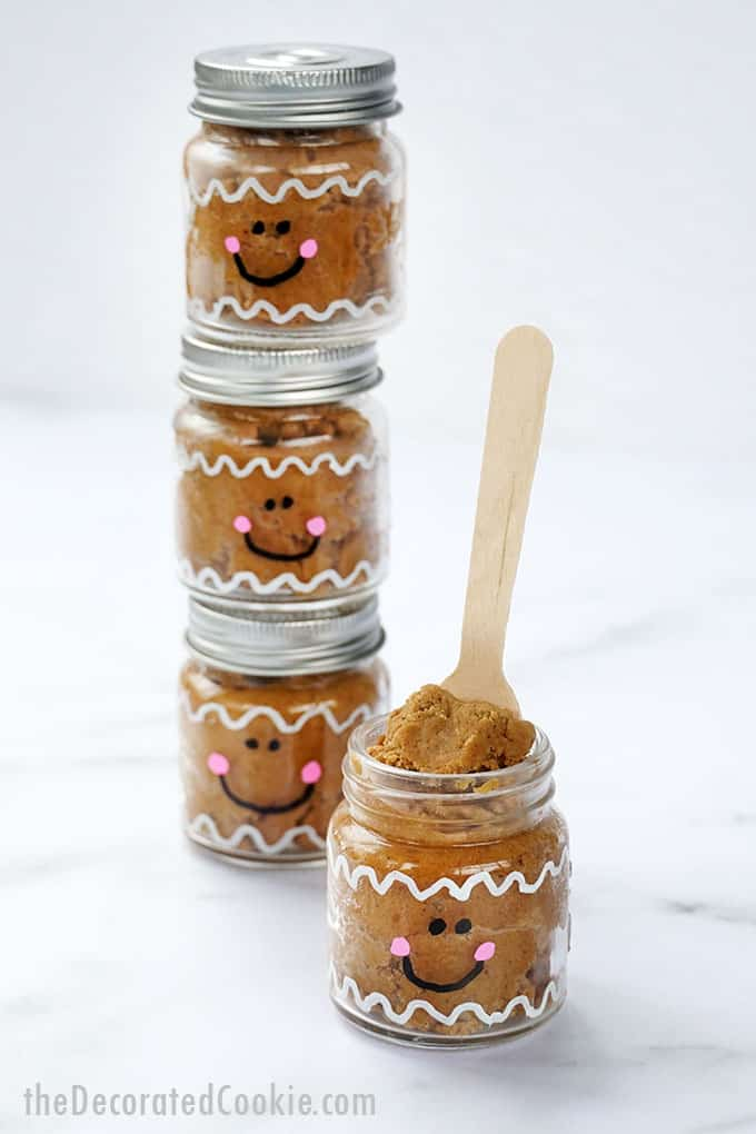 stacked edible gingerbread cookie dough in little mason jars painted as gingerbread men