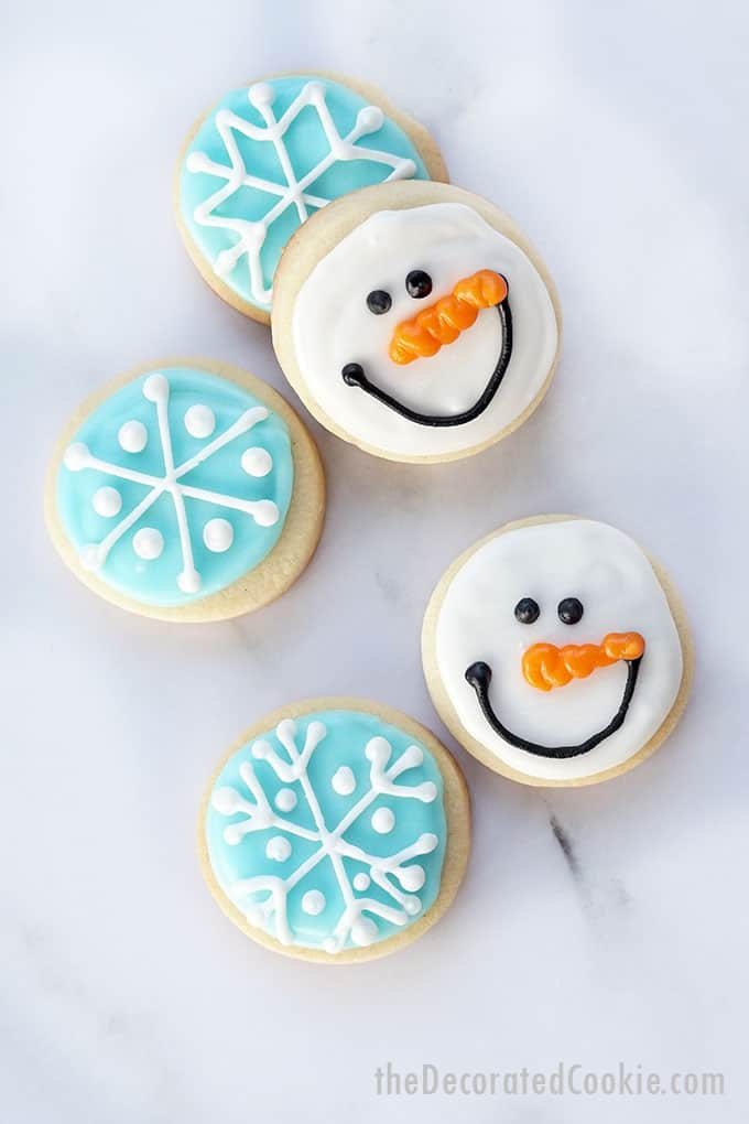 close-up of mini snowflake and snowman cookies