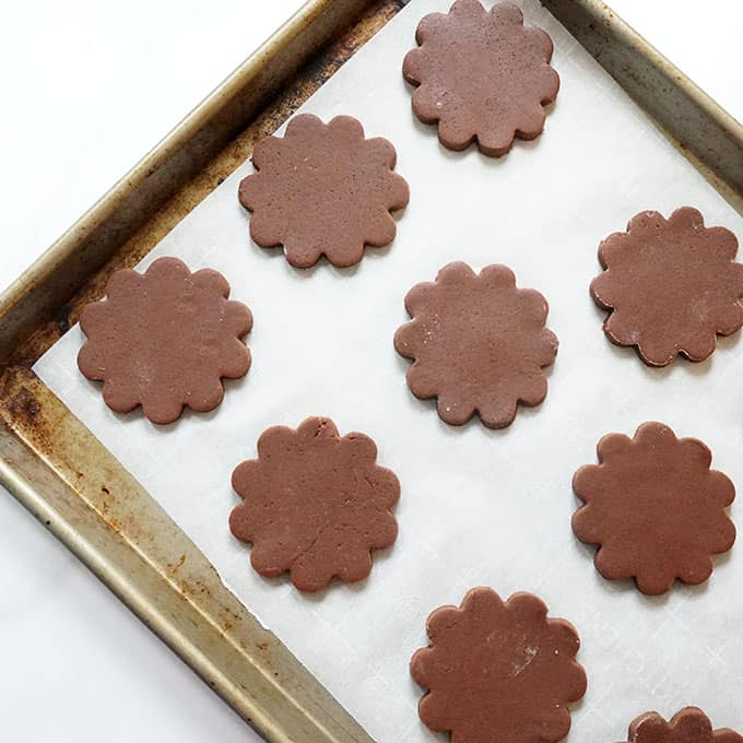 cut-out chocolate sugar cookie flowers on baking tray