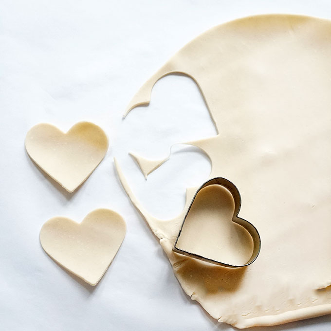 cutting out hearts from pizza dough for valentine's day hand pies