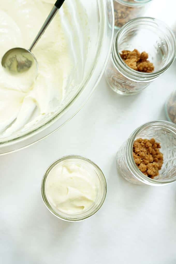 assembling vanilla and chocolate pudding pie in a jar